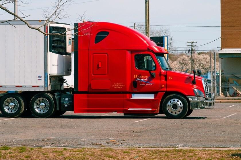Crveni kamion sa belom prikolicom na parkingu
