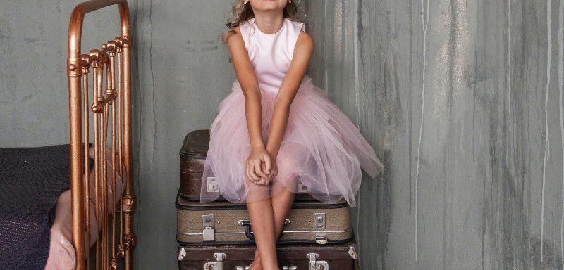 Devojčica koja sedi na koferima
