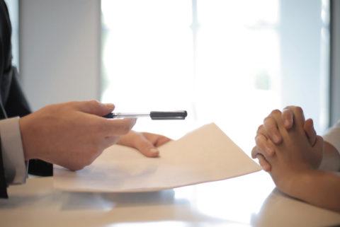 prikaz ruke čoveka koji sagovorniku pruža hemijsku za potpisivanje ugovora