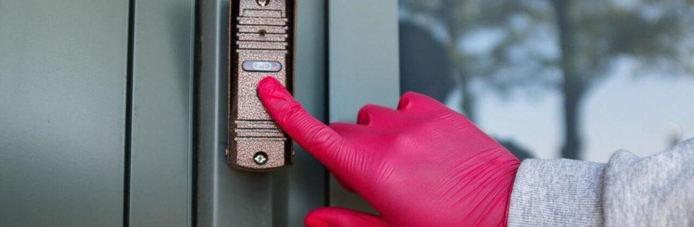 ruka sa gumenom rukavicom stiska dugme za lift